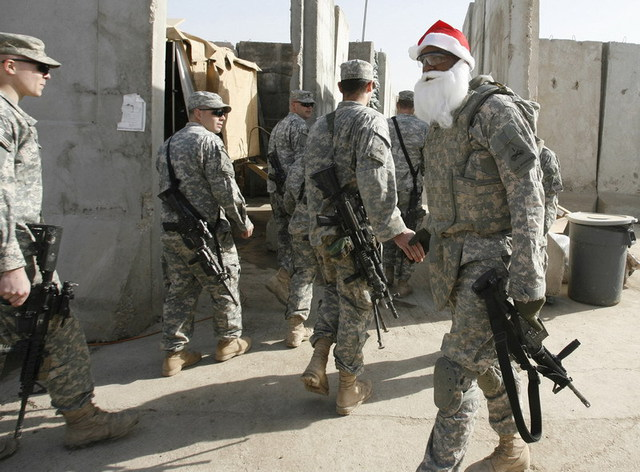 U.S. soldiers look at fellow soldier wearing Santa Claus mask during Christmas Day at U.S. military patrol base in Baghdad's Sadr City  Via Erik de Castro / Reuters