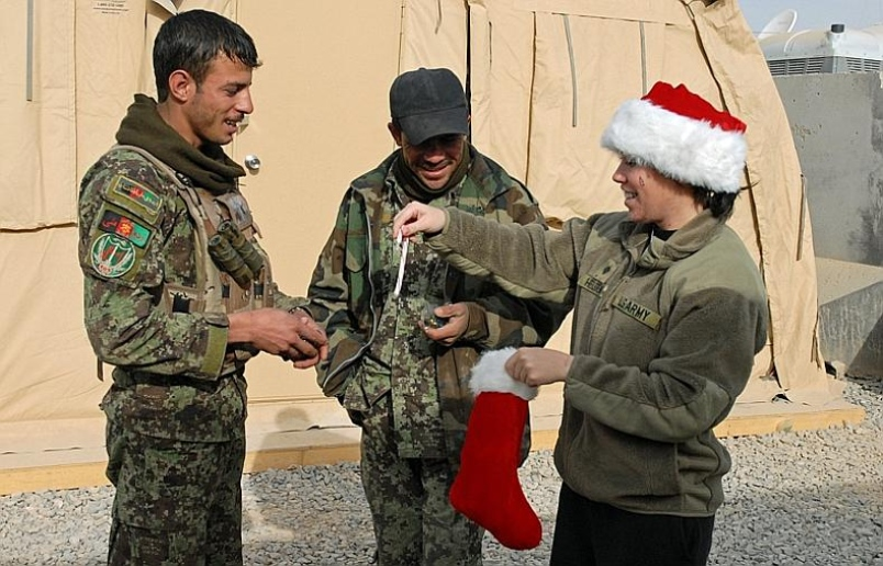 Spc. Lindsey Helgemo, 23, hands out candy canes from a stocking to amused Afghan National Army soldiers on Christmas morning at Combat Outpost Terra Nova in the Arghandab district of Kandahar province, Afghanistan. via Stars and Stripes
